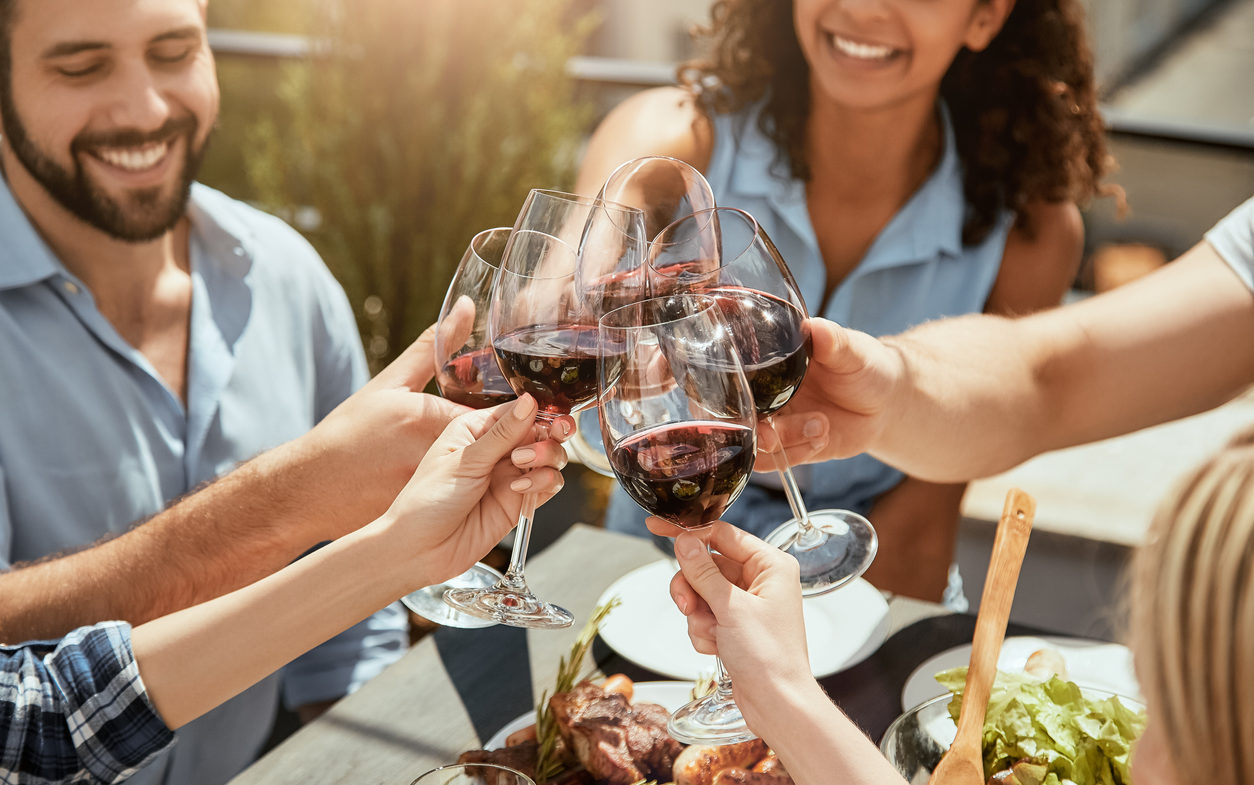 Celebrating friendship! Group of happy young people are eating fresh food, talking and clinking glasses with wine while having picnic outdoors. Weekend concept. Summer time. Friendship.